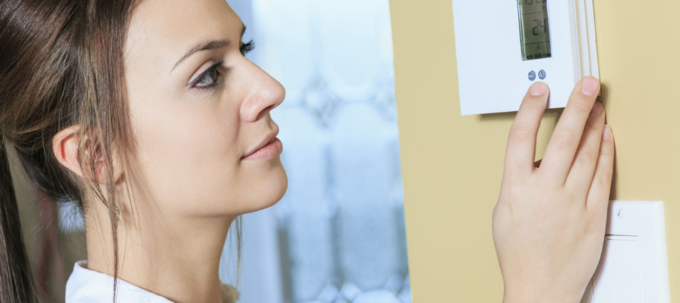 Woman Sets Home Heating & Air Thermostat